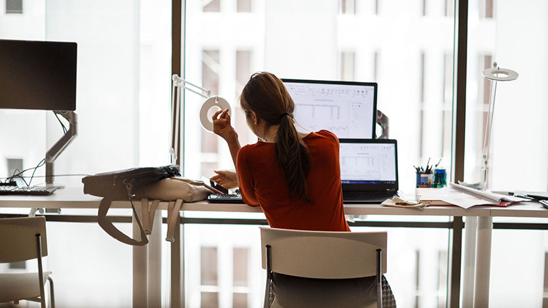 A woman sitting at a desk in front of a laptop and monitor with high-rise view.