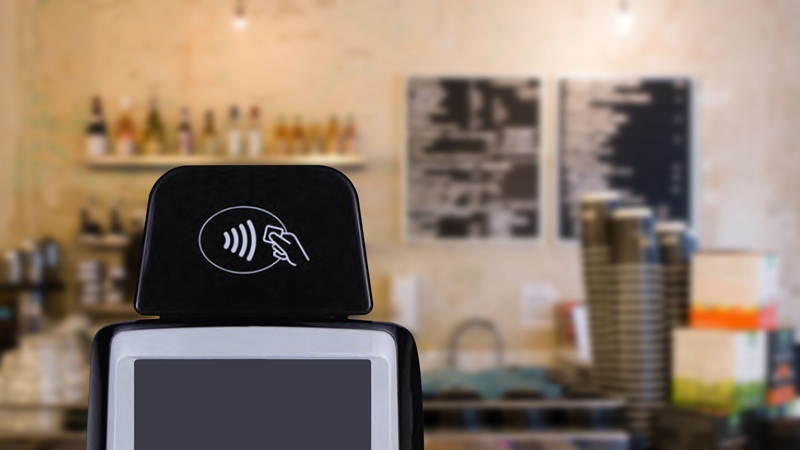 Closeup of a POS system in a coffee shop displaying the Tap to Pay logo.