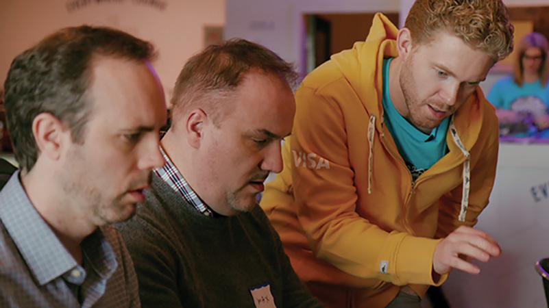 Three men, one in a Visa yellow jacket, another a gray sweater, and another in plaid, talk amongst each other.